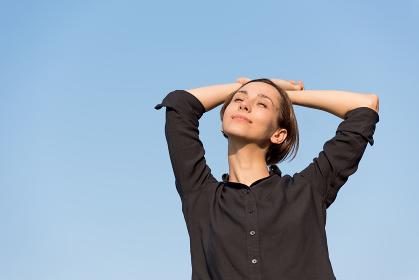 青空の下でリラックスする若い女性