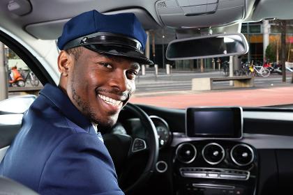 Happy Male Chauffeur Sitting Inside Car
