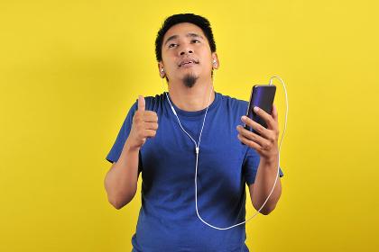 Asian man in casual blue t-shirt wearing headset listening to mu , Kotabangun, East Kalimantan, Indonesia