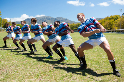 Full length of rugby players playing tug of war on grassy field