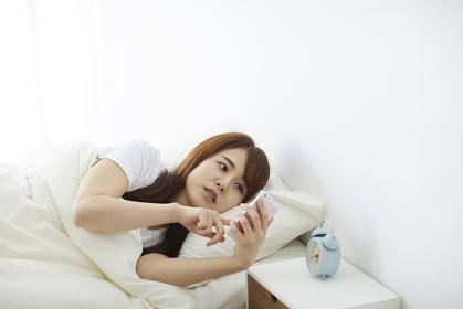 ベッドで横になりながらスマートフォンを見る日本人女性