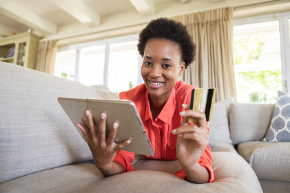 Mixed race woman spending time at home, lying on couch, using tablet while online shopping. Self isolating and social distancing in quarantine lockdown during coronavirus covid 19 epidemic.