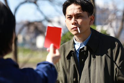 レッドカードを出される歩きタバコの男性