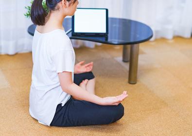 自宅でオンライン配信動画を見ながらヨガで運動不足解消に励む若い女性【ニューノーマルのライフスタイル】