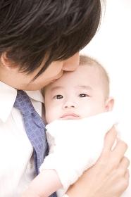 赤ちゃんにキスする父親