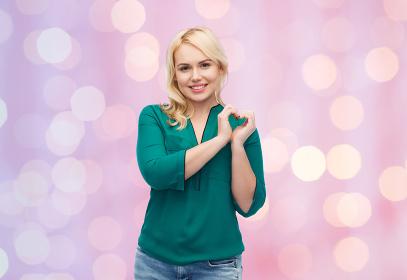 smiling young woman in shirt showing heart shape