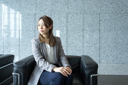 建物のロビーのソファに座る女性