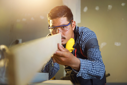 Selective focus of handsome man in goggles and apron in workshop