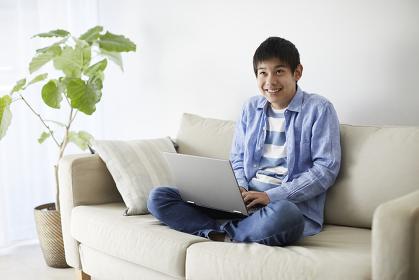 ノートパソコンを操作する10代の男の子