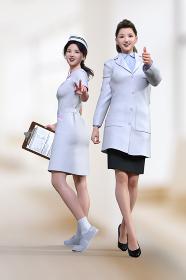 日差しが差し込む院内の廊下で日本人女性の医師と看護師が笑顔でグッドサインとピースサインをしている