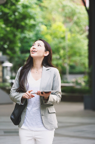 ビジネス街を歩く女性 タブレットを持つ