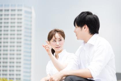 ビジネス街で座って会話するカップル