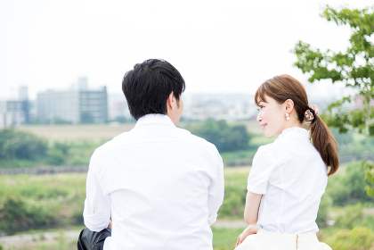 屋外で笑顔で会話する若い男女