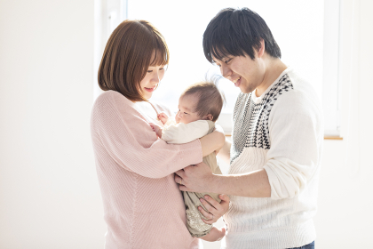 明るい部屋の中で赤ちゃんを抱っこするお父さんとお母さん