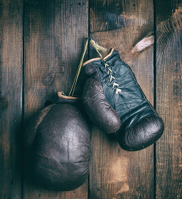 very old shabby leather boxing gloves hanging on a nail