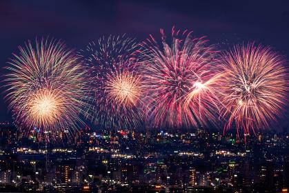 夜の町並みに打ち上がる花火のイメージ
