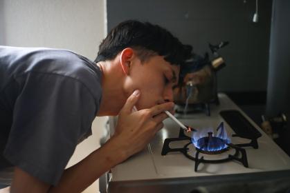 ガスコンロでタバコに火をつける男性