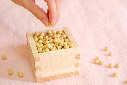 枡と大豆をつまむ女性の手