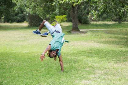 Hipster doing back flip in the park
