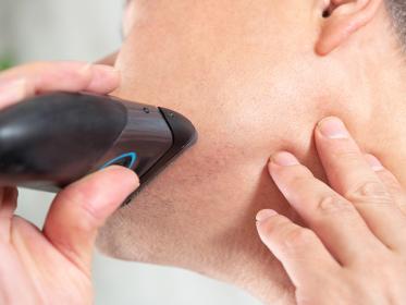 電気シェーバーで剃りにくい箇所の髭を剃る男性ビジネスマン