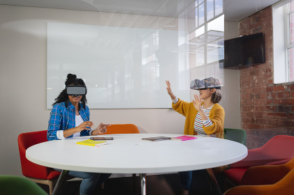 Diverse female colleagues sitting at work wearing virtual reality set and playing. independent creative design business.