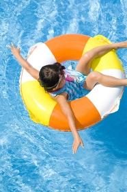 浮き輪でプールに浮かぶ水着姿の女の子
