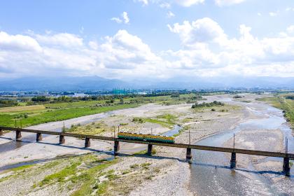 北アルプスを背景に常願寺川を渡る富山地方鉄道本線の普通列車