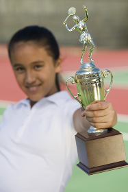 Young girl on tennis court holding trophy focus on trophy