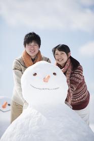 雪だるまの側で微笑むカップル