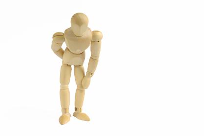 腰が痛いポーズをした前向きの木製のモデル人形