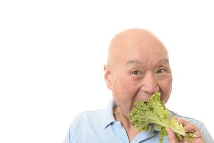 野菜を笑顔で食べるシニア