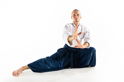 Aikido master practices defense posture. Healthy lifestyle and sports concept. Man with beard in white kimono on white background.