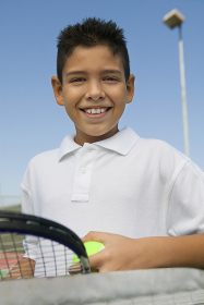 Young boy with tennis racket and ball at net on tennis court portrait close up