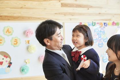 変顔をする幼稚園児の女の子と両親