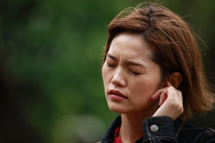 耳に違和感を感じる女性