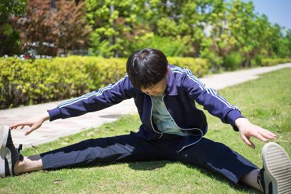 芝生の上でストレッチをする男性