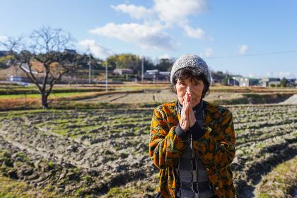 田舎でお祈りをする高齢の女性