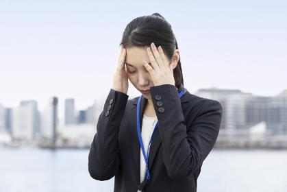 ストレスを抱えた表情をするアジア人のビジネスウーマン