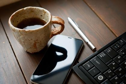 デスクの上のコーヒーとスマートホン