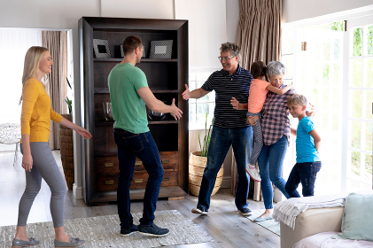 Caucasian family spending time together at home, standing in the sitting room, welcoming a senior Caucasian couple entering the house.