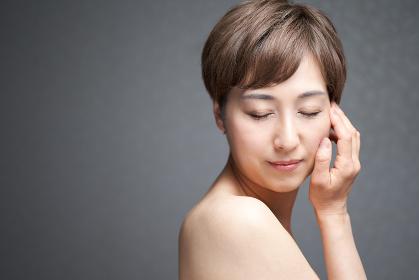 頬に手を当てて目をつぶる中年の日本人女性