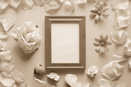 セピア色の造花に囲まれた中央に縦長の木製フォトフレームと白いコピースペース。平置きの俯瞰撮影。