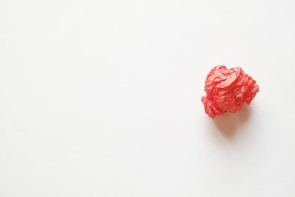 灰色の紙の右側に置いた赤色の紙礫とコピースペース