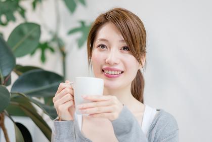 コーヒーカップを手にこちらを見つめる女性