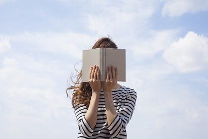 本で顔を隠す日本人女性