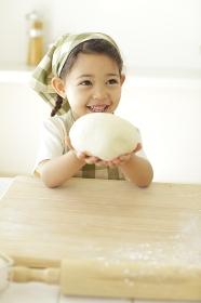 パン生地を手に持つ小さな女の子