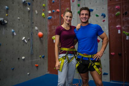 Portrait of male trainer with female athlete standing by climbing wall