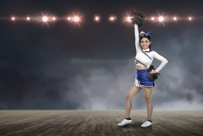 Attractive asian cheerleader holding pom-poms