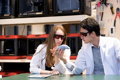 3Dプリンターで作成したカバのオブジェを観察する男女