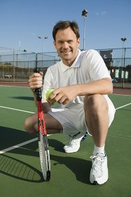Man crouching on Tennis Court holding tennis racket and ball portrait